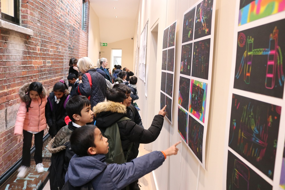 Canon Barnett School pupils look at their foil art on display