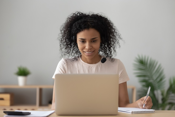 Young black woman e-learning making notes looking at laptop